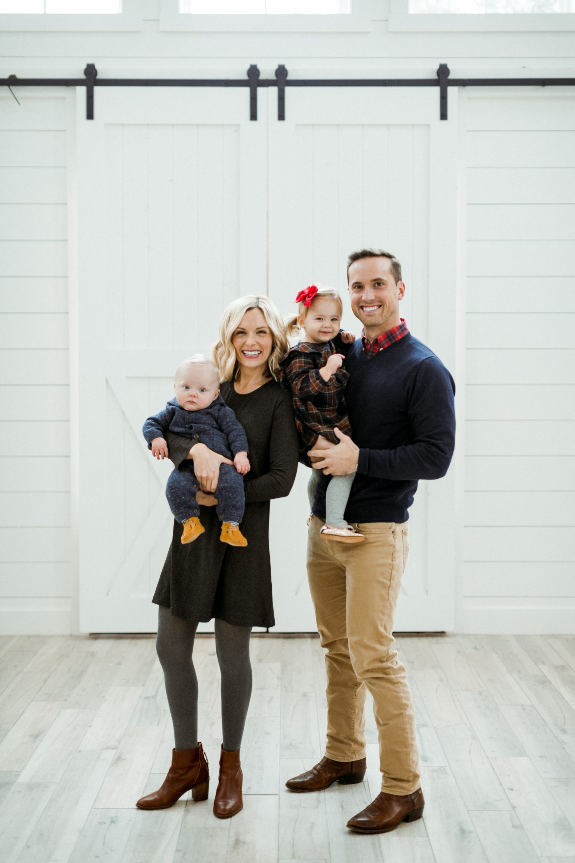 Dillon Meek and family photo in front of white barn door